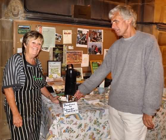 John gives Hilary the donation for Tod food drop in