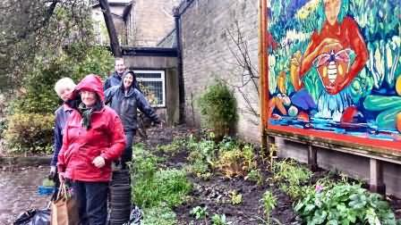 Shirley, Jenny, Sam and Peter get soaked planting library lock