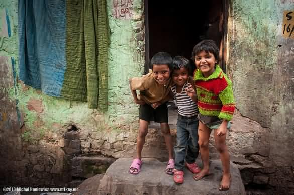 children smiling in a slum